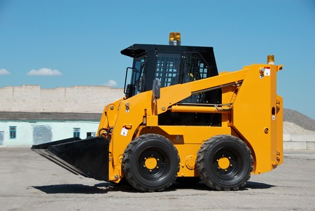 compact track loader: skid steer loader construction machine with bucket outdoors