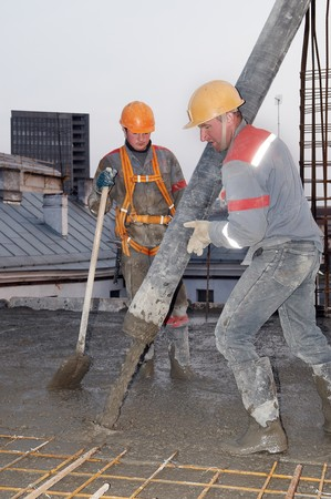 builder workers aiming pump tube during concrete pouring process Stock Photo - 7177726