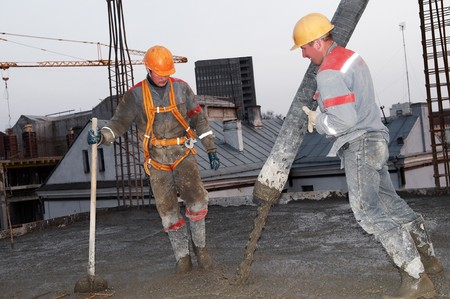 taskmaster: builder workers aiming pump tube during concrete pouring process