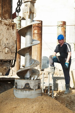 poling: worker controlling piling process tube in metal form for continuous concrete casting Stock Photo