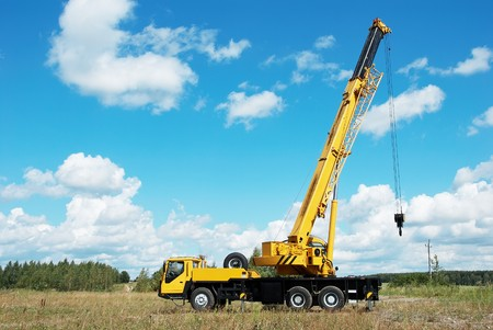 mobile crane: yellow automobile crane with risen telescopic boom outdoors over blue sky