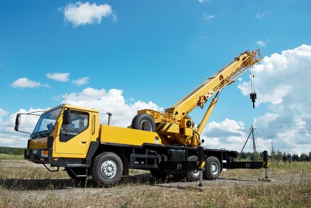 camion gru: yellow automobile crane with risen telescopic boom outdoors over blue sky