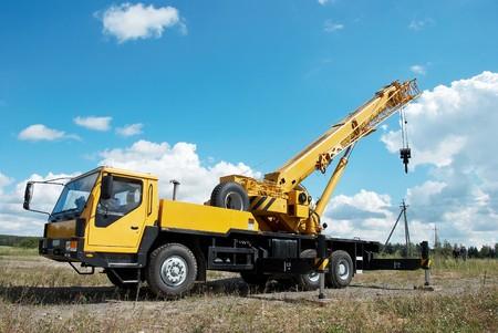 cranes: yellow automobile crane with risen telescopic boom outdoors over blue sky