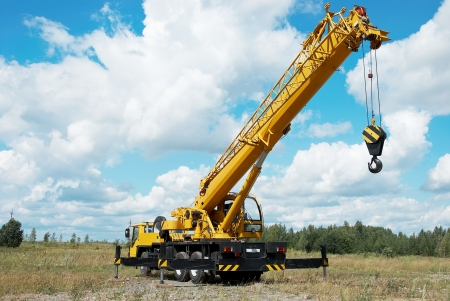 yellow automobile crane with risen telescopic boom outdoors over blue sky
