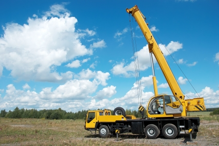 loaders: yellow automobile crane with risen telescopic boom outdoors over blue sky