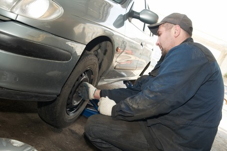 compressed air: repairman making tyre fitting with air compressed wrench (screwing up bolts)