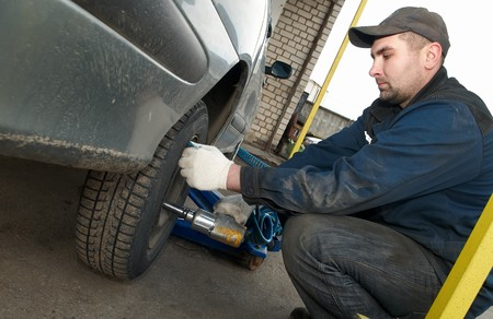 replacements: repairman making tyre fitting with air compressed wrench (screwing up bolts)