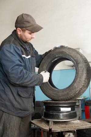 greasing: serviceman repairman worker lubricating car tyre at workshop Stock Photo