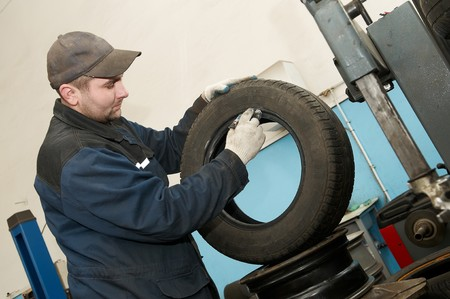 serviceman repairman worker lubricating car tyre at workshop photo