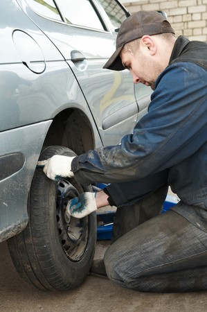tire fitting: repairman making tyre fitting with air compressed wrench (screwing up bolts)