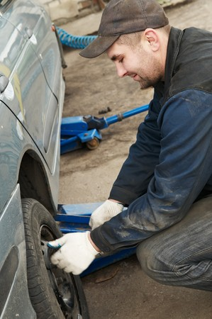 repairman making tyre fitting with air compressed wrench (screwing up bolts) photo