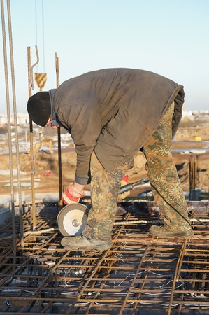 cutoff: worker in cutting metal reinforcing lattice with abrasive cutoff saw disk