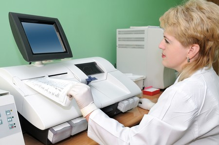 archiving: woman medic doctor in uniform working at blood test radiometer equipment Stock Photo