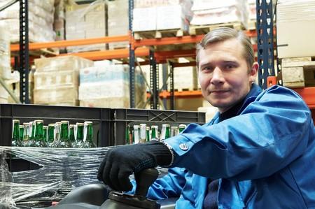 carretillas almacen: Controlador de trabajador de un cargador de montacargas en ropa de trabajo azul en almac�n