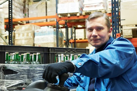 warehouse equipment: Worker driver of a forklift loader in blue workwear at warehouse