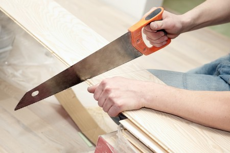 timber cutting: closeup work operation of cutting wood furniture by hand saw Stock Photo