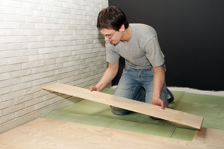 Young worker laying a floor with laminated flooring boards photo