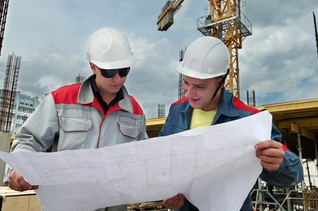 Two engineer builders examining blueprint at construction site photo