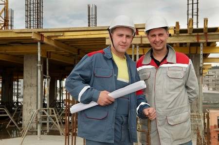 foremaster: Two engineer builders with blueprint at construction site Stock Photo