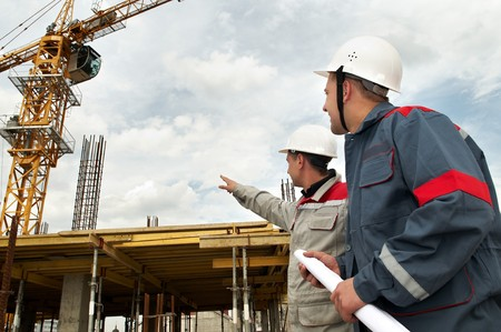 site construction: Two engineer builders with blueprint at construction site Stock Photo