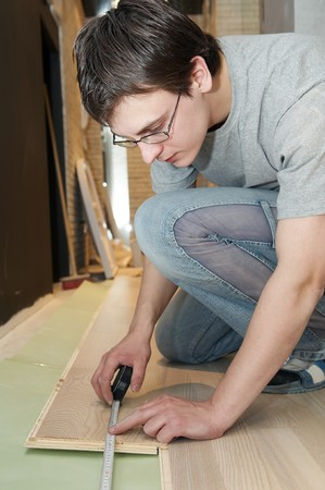Young worker carpenter measuring while laying a floor with laminated flooring boards photo
