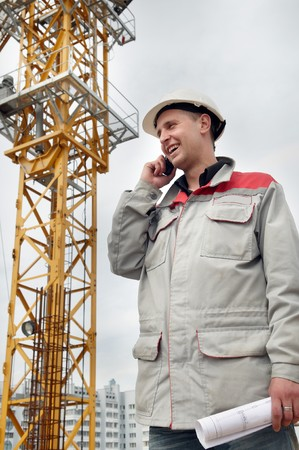 One happy engineer builder with blueprint at construction site speaking on mobile phone photo