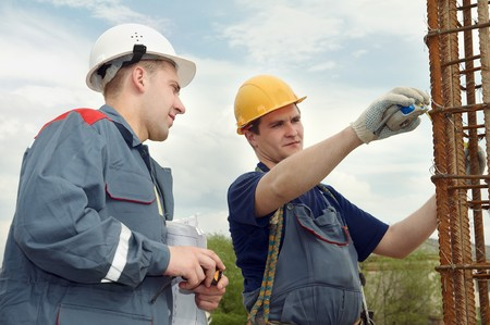 taskmaster: two builders workers checking with measure tape reinforcement column Stock Photo