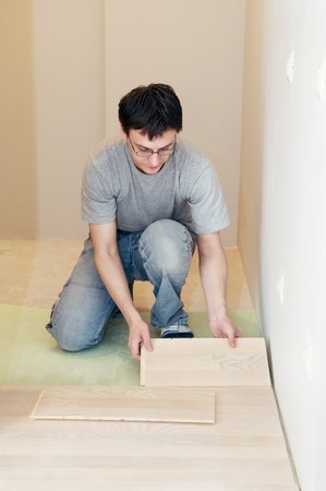 Young worker carpenter laying a floor with laminated flooring boards  photo