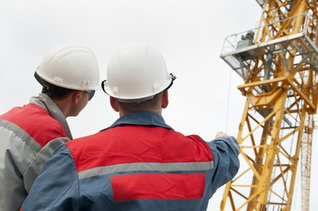 Rear view of two engineer builders at construction site directing to the tower crane photo