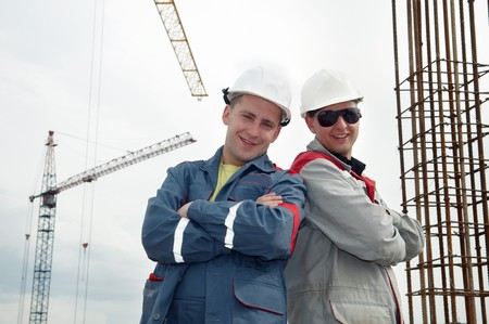 Two happy and smiling engineer builders at construction site photo