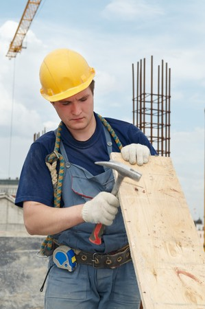 Worker builder at construction site working with plywood board and hammer photo