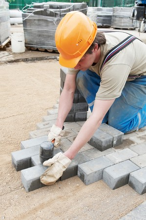 banquette: mason worker making sidewalk pavement with stone blocks