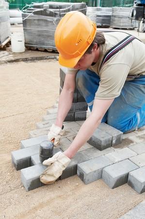 work path: mason worker making sidewalk pavement with stone blocks