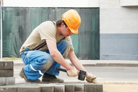 constructor: trabajador de Mason, haciendo el pavimento de la acera con bloques de piedra