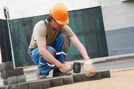 mason worker making sidewalk pavement with stone blocks photo