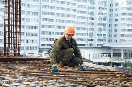 worker in workwear making reinforcement metal framework for concrete pouring Stock Photo - 7398157