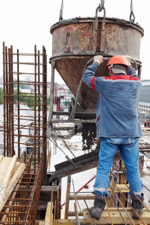 construction building worker at construction site pouring concrete in form photo
