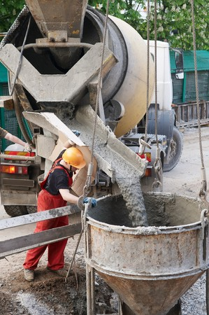 foremaster: worker builder controlling concrete filling process at construction site