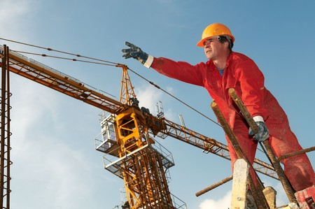 millwright: builder worker in red uniform at construction site directing a crane Stock Photo