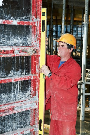 worker builder in red uniform checking vertical by level measurement tool photo