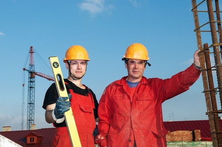mounter: two builder workers in red uniform at construction site
