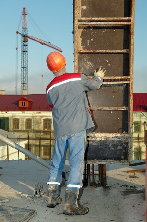 mounter: Builder worker installing formwork boxes for concrete pouring at construction site Stock Photo