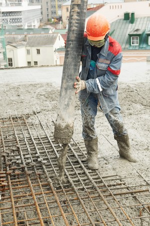 concrete form: builder worker aiming pump tube during concrete pouring process