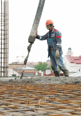 taskmaster: builder worker aiming pump tube during concrete pouring process