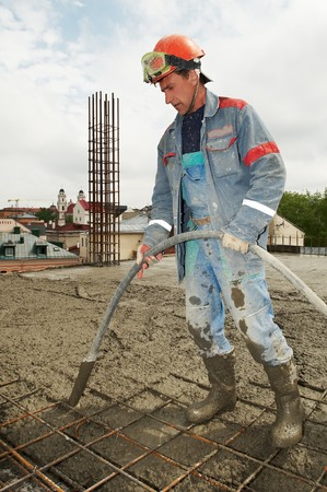 concrete form: builder worker with vibration machine  compacting poured concrete