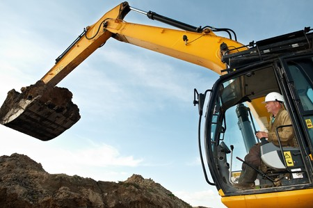 open cast mine: excavator loader driver working at construction building area
