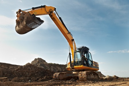 open cast mine: Loader Excavator standing in sandpit with risen bucket over cloudscape sky