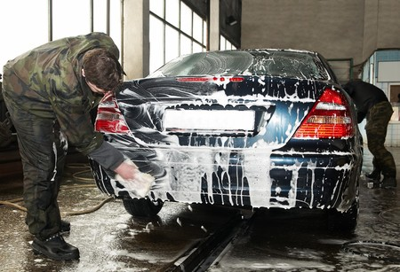 car cleaning: manual car washing cleaning with foam and water at service station Stock Photo
