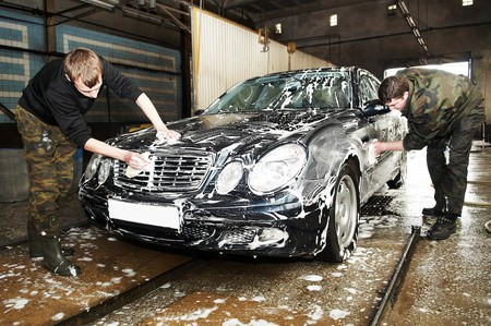 car service: manual car washing cleaning with foam and water at service station Stock Photo