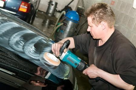 car polish: car care work with machine polisher at service station